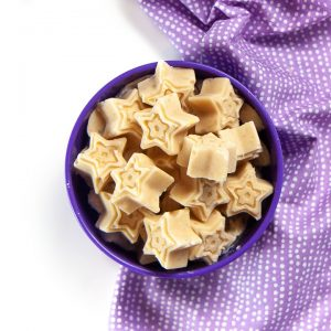A purple bowl filled with star shaped peanut butter banana melts for baby.