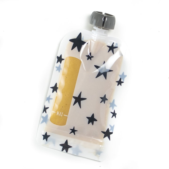 Reusable baby food pouch with banana and peach puree inside.