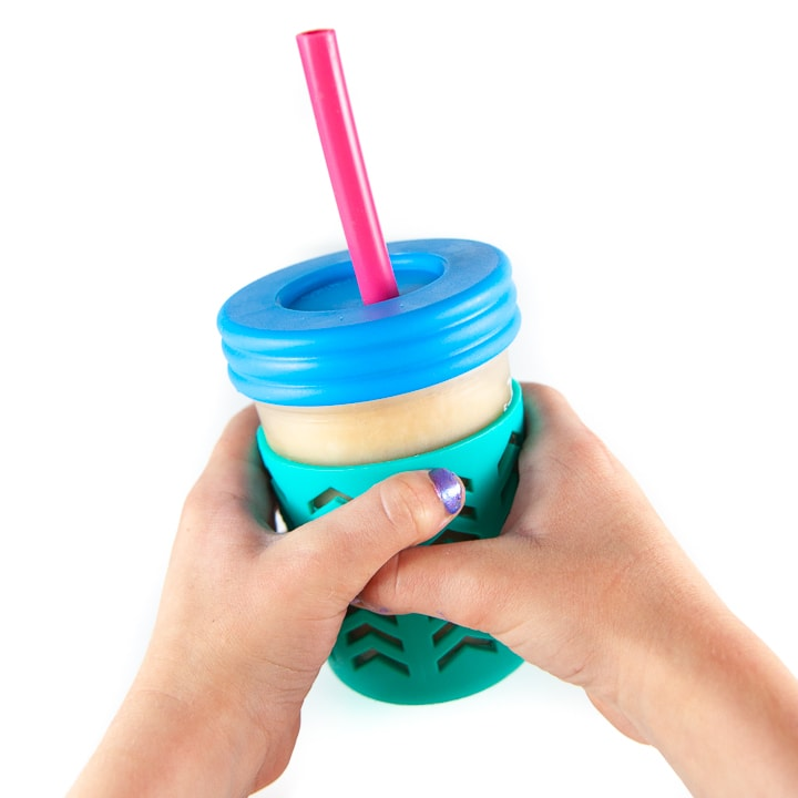Kids hands holding up smoothie cup.