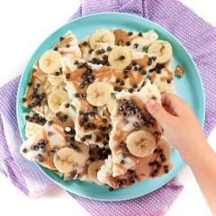 small hand reaching for a piece of peanut butter banana frozen yogurt bark.