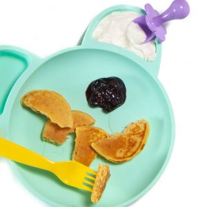 plate full of baby-led weaning pancakes cut into pieces with a fruit dip.