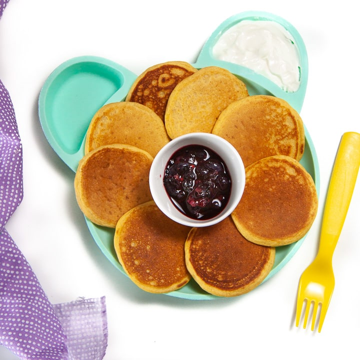 Plate full of sweet potato pancakes for baby with a fruit and yogurt dip.