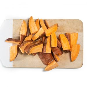 Cutting board with cut sweet potato wedges.