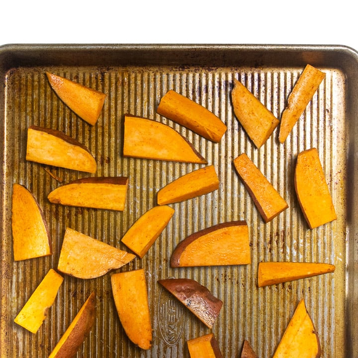 Baking sheet with raw sweet potatoes.