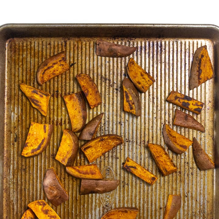 Sweet potato on a baking sheet, roasted in the oven.