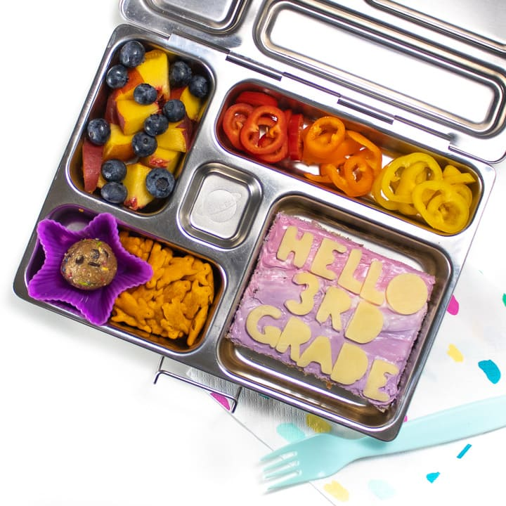 A silver bento school lunch box with a fun and colorful lunch for the first day of school.