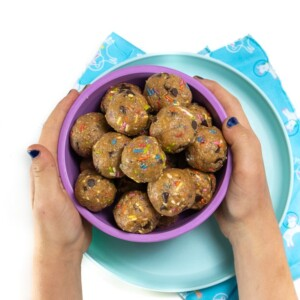 Small kids hands holding a bowl of funfetti energy balls.