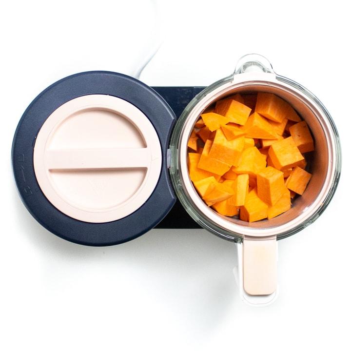 Black and pink Beaba babycook machine with chunks of sweet potato inside.