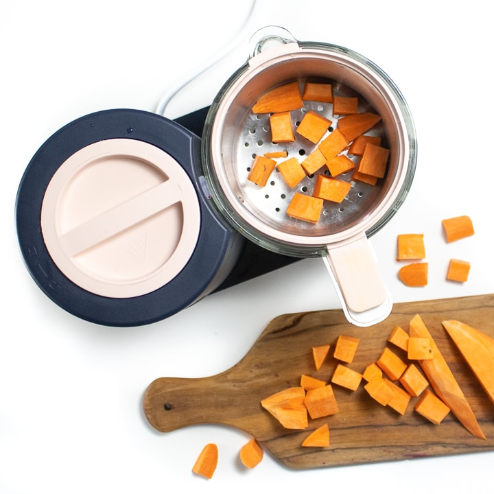 Spread showing Beaba babycook with a cutting board next to it with chopped sweet potato.