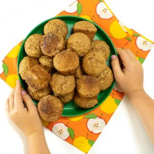 Small kids hand holding a plate of mini applesauce muffins.