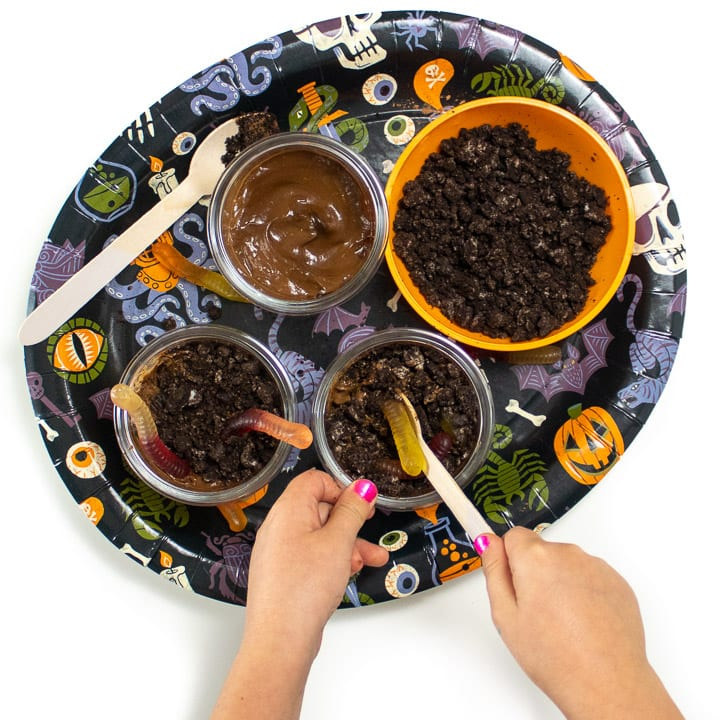 Halloween plate filled with ingredients to make avocado dirt pudding with small hands making it.