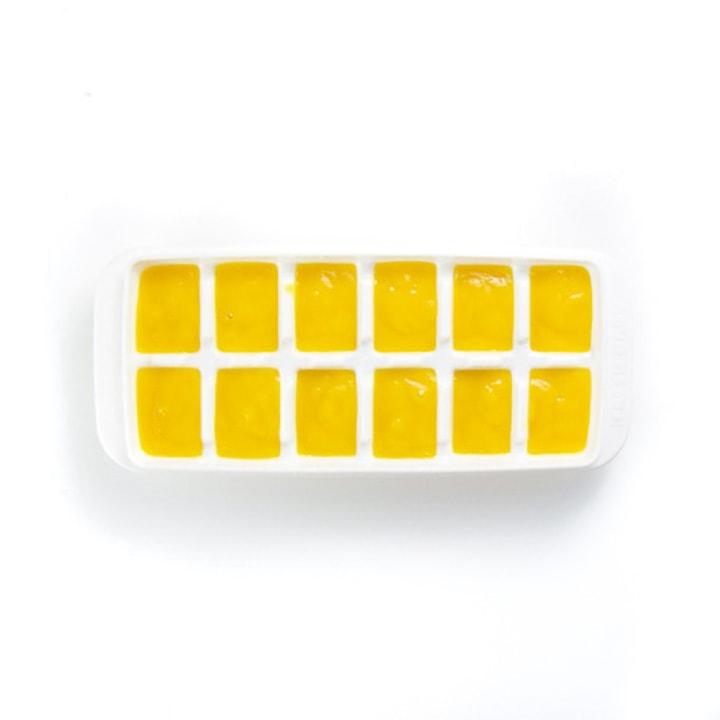 white ice cube tray full of yellow mango puree.