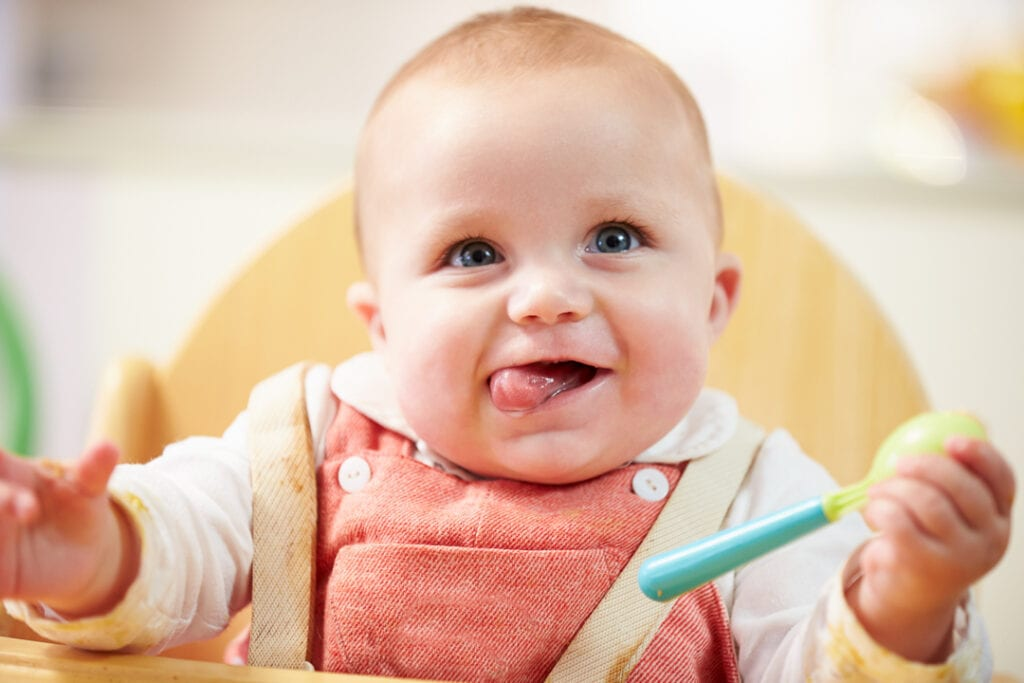 Baby girl in a high chair holding a spoon.