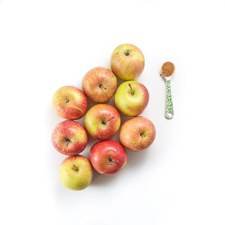 apples on a white surface with a green spoon with cinnamon next to it.
