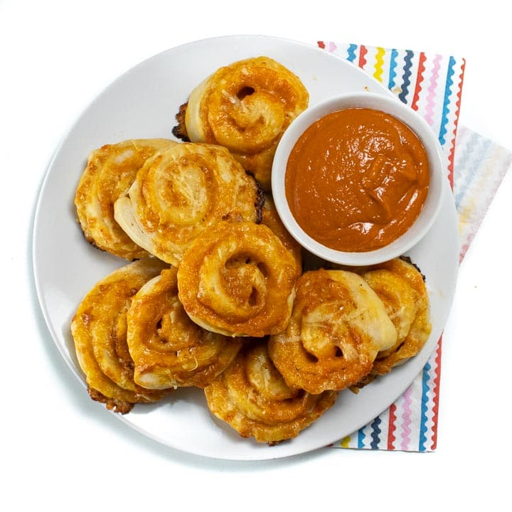 Plate of veggie hidden pizza rollups with a side of sauce ready for kids to take and eat.