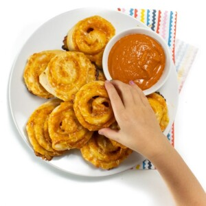 Hand reaching over a plate of veggie hidden pizza rollups with a side of sauce ready for kids to take and eat.