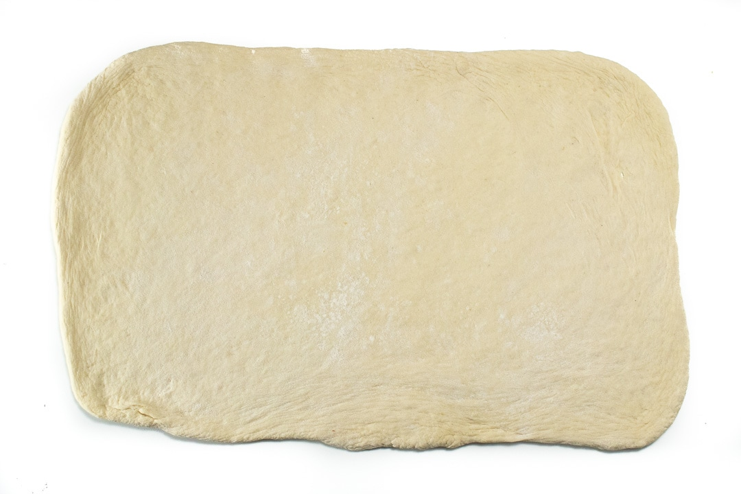 pizza dough rolled out into a rectangle.