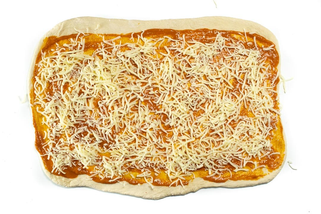 Pizza dough in a rectangle with hidden veggie sauce and cheese.