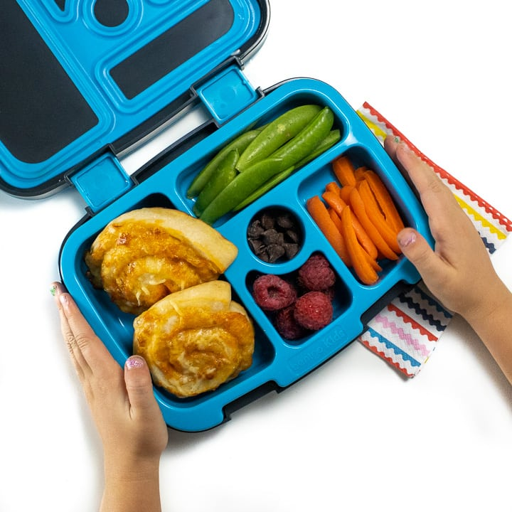 Small kids hands holding a lunch box with pizza rollups inside.