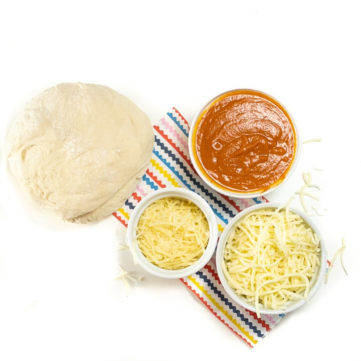 Ingredients in a spread on a colorful napkin with ingredients for hidden veggie pizza rollups.