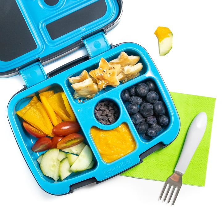 Bento box filled with a veggie loaded hummus with other healthy ingredients for toddlers and kids.