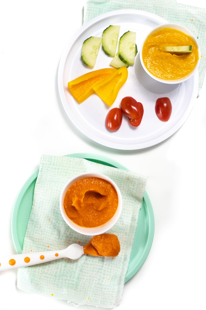 Two different plates with recipe on them - one is a veggie loaded dip for toddler and the other is a small bowl of veggie loaded puree for baby.