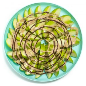 Plate of apple slices with a healthy caramel sauce and melted chocolate onto.