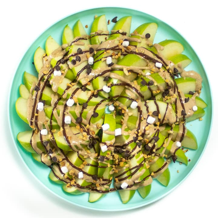 Plate with apple nachos with healthy caramel, melted chocolate and topping.