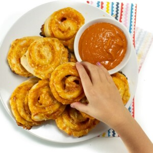 Small kids hand reaching for the pizza pinwheels on a plate.