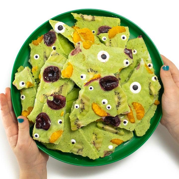 Small hands holding a plate of monster frozen yogurt bark.