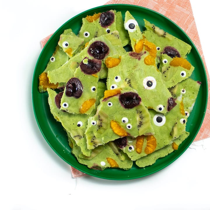 Plate of green monster frozen yogurt bark ready for kids to eat it for halloween.