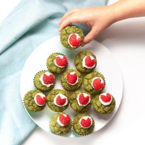 Small hand grabbing a green grinch mini muffin.