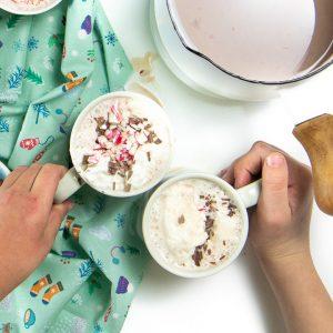 2 hands grabbing mugs of hot chocolate.