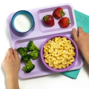 Hands holding a Purple school tray with instant pot Mac and cheese, broccoli and strawberries for a toddler or kid.