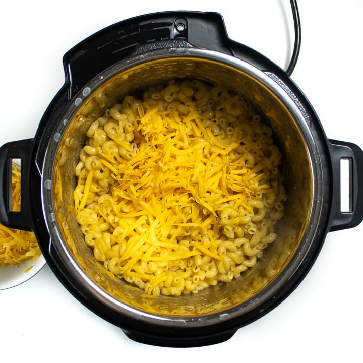 Instant pot with cooked noodles and shredded cheese.