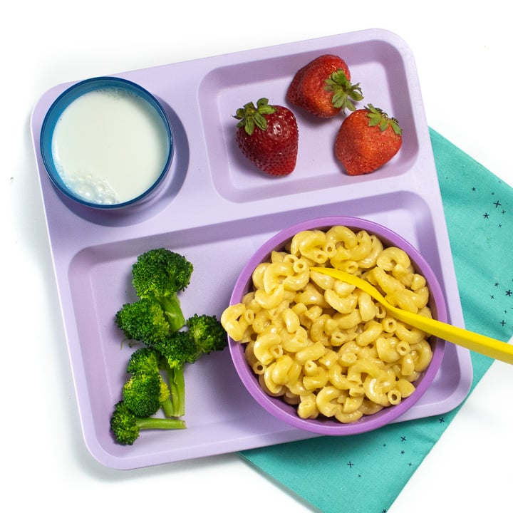 Purple school tray with instant pot Mac and cheese, broccoli and strawberries for a toddler or kid.