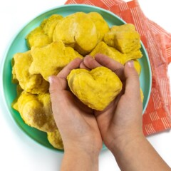 Small kid hands holding a heart shaped pumpkin biscuit.