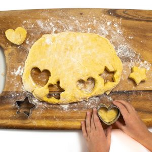 kid hands cutting out a heart shaped biscuit.