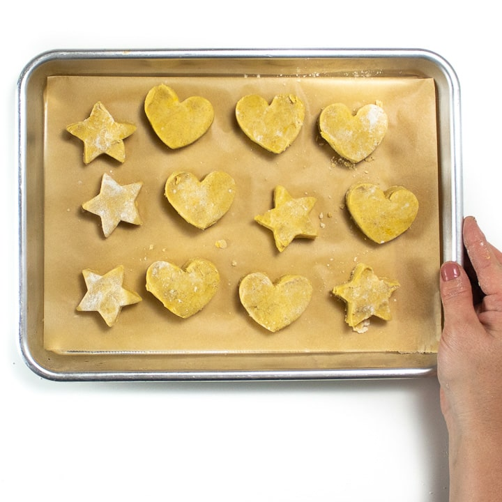 Hand holding a small baking sheet full of heart and star shaped pumpkin biscuits for kids.