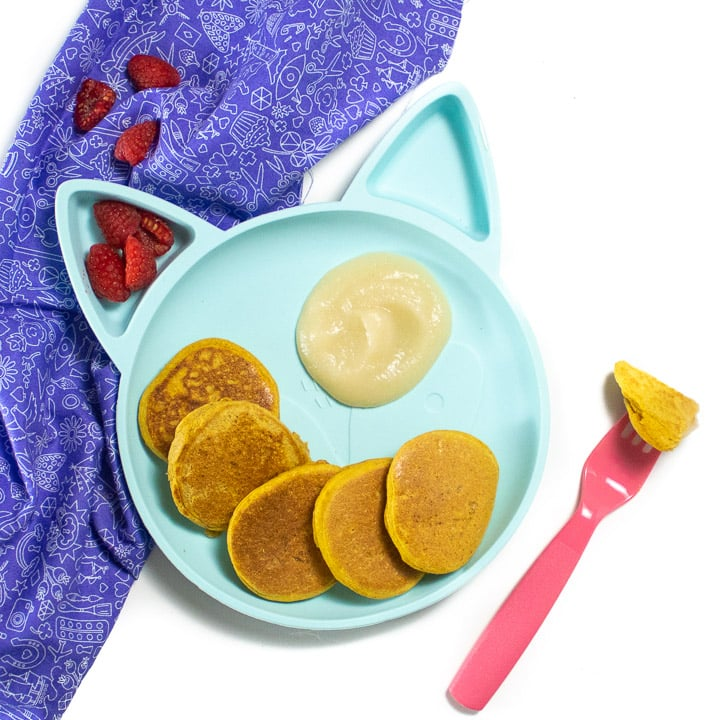 Plate of pumpkin pancakes for baby and toddler with a pear dipping sauce.