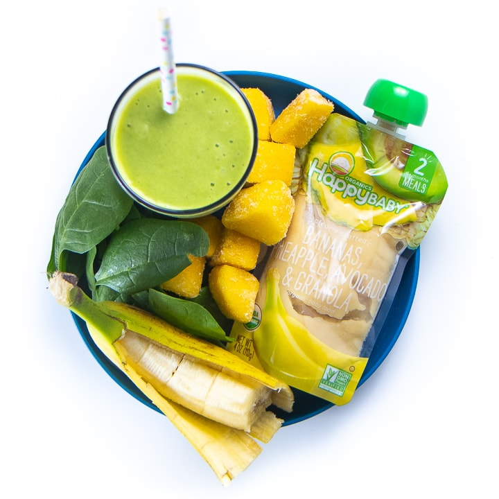 Green smoothie surrounded by a plate full of the healthy ingredients used to make it.