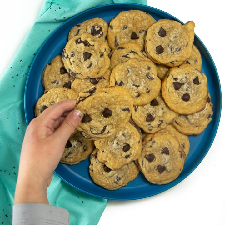 Small kids hands holding a whole wheat chocolate chip cookie over a plate of cookies.