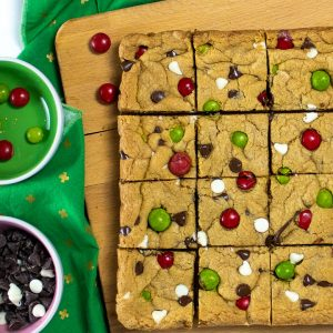 Cookie bars on a cutting board cut into squares.