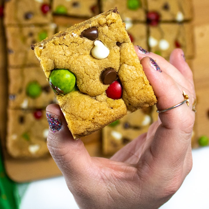 Hand holding up a Christmas cookie bar.