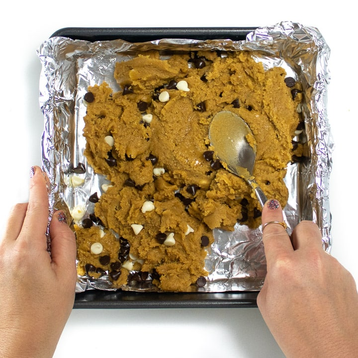 Hands pressing down the cookie dough into the pan.
