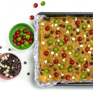 Christmas cookie bar dough with candy and chocolate chip toppings getting put on the top of it.