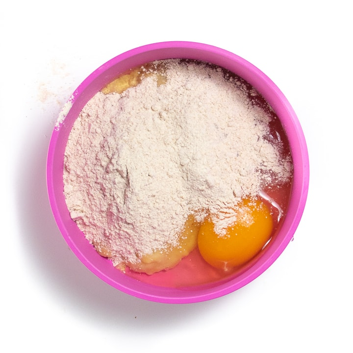 Small pink bowl with 3 ingredients for banana pancakes.