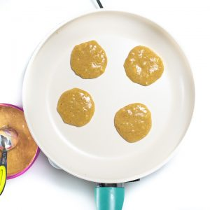 Pan with banana pancakes cooking.