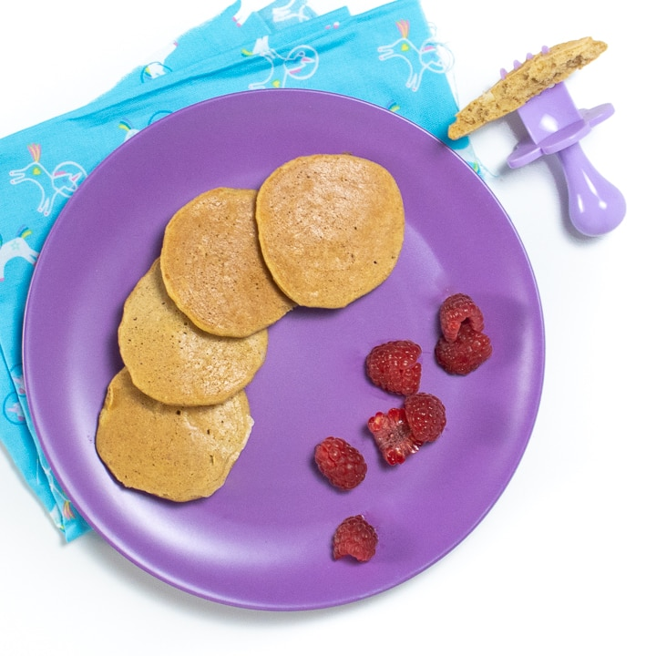 Purple plate with banana pancakes and raspberry pieces for baby.
