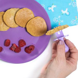 Hand holding a piece of banana pancakes for baby or toddler.